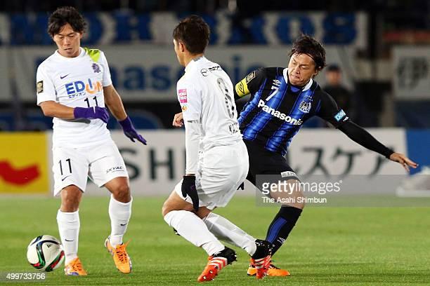 Yasuhito Endo of Gamba Osaka and Kazuyuki Morisaki of Sanfrecce Hiroshima compete for the ball during the JLeague Championship Final frist leg match...
