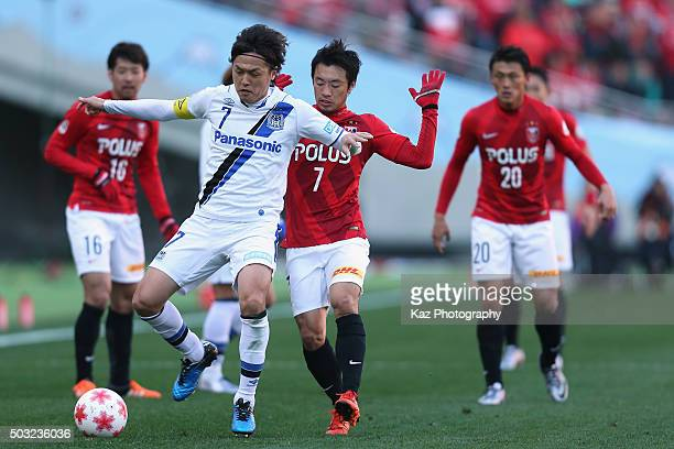 Yasuhito Endo of Gamba Osaka and Tsukasa Umesaki of Urawa Red Diamonds compete for the ball during the 95th Emperor's Cup final between Urawa Red...