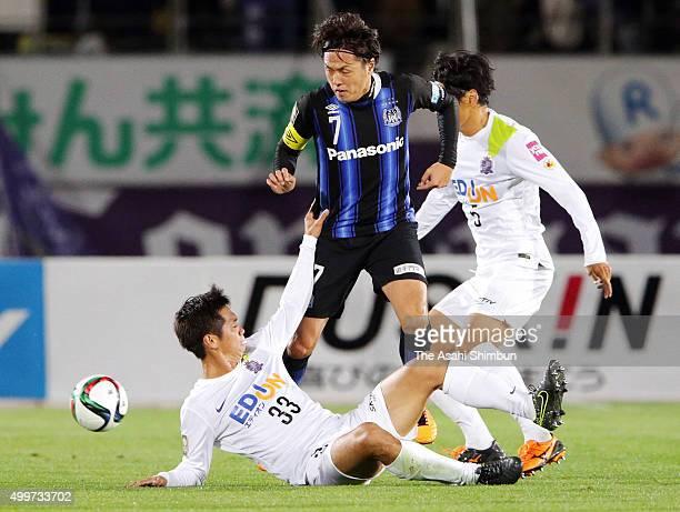 Yasuhito Endo of Gamba Osaka competes for the ball against Tsukasa Shiotani and Kazuhiko Chiba of Sanfrecce Hiroshima during the JLeague Championship...