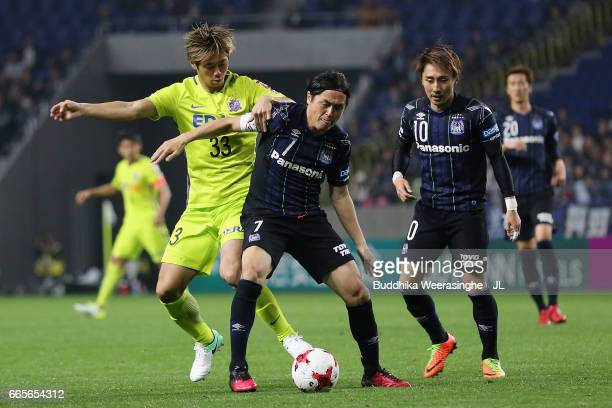 Yasuhito Endo of Gamba Osaka controls the ball under pressure of Tsukasa Shiotani of Sanfrecce Hiroshima during the JLeague J1 match between Gamba...