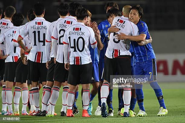 Yasuhito Endo of Gamba Osaka hugs Cha Du Ri of FC Seoul after the AFC Champions League Round of 16 match between Gamba Osaka and FC Seoul at Expo '70...