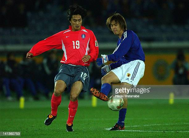 Yasuhito Endo of Japan and Ahn JungHwan of South Korea compete for the ball during the East Asian Football Championship match between Japan and South...