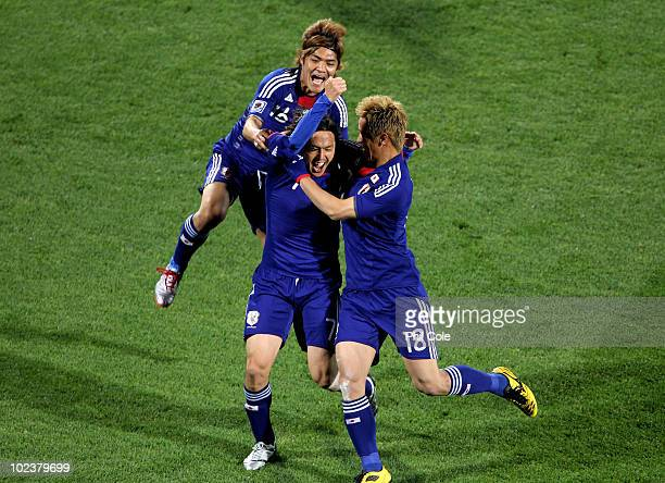Yasuhito Endo of Japan celebrates scoring his team's second goal from a free kick with Yoshito Okubo and Keisuke Honda of Japan during the 2010 FIFA...