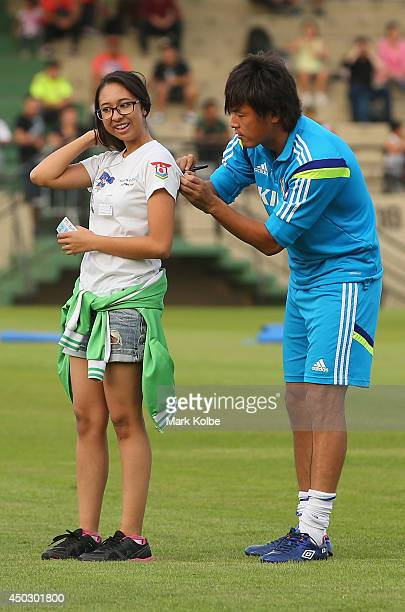 Yasuhito Endo signs an autograph as the team pose for a group photo with children from the local community during a Japan training session held at...