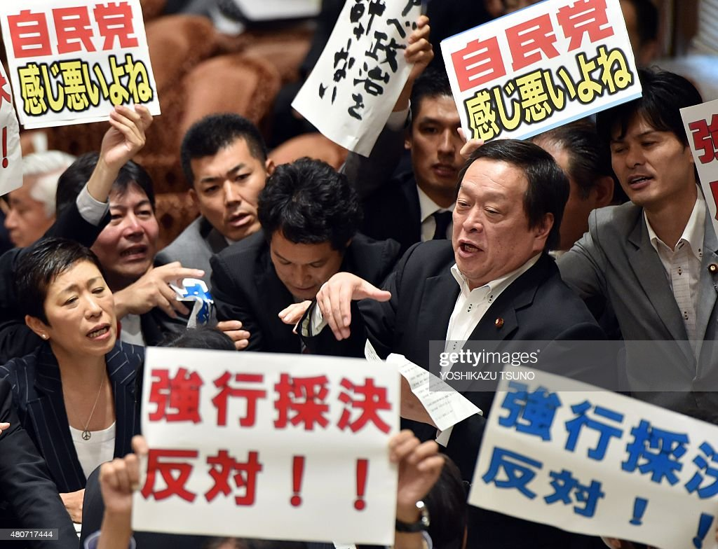 Yasukazu Hamada (2nd R), chairman of a parliamentary panel on Japanese Prime Minister Shinzo Abe's controversial security bills, is surrounded by opposition lawmakers holding placards which say 'Opposed to forced passage of the bills', during a parliamentary committee discussion on the bills at the National Diet in Tokyo on July 15, 2015. Abe made another pitch on July 15 for security bills which would beef up Japan's military, as he pushed legislation through a key panel despite surging public and parliamentary opposition. The controversial bills that would expand the remit of the country's armed forces were approved by the lawmakers of the ruling coalition. AFP PHOTO / Yoshikazu TSUNO