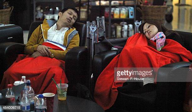 Yasuke Imazu and his wife Yuka of Tokyo Japan sleep in Terminal D at DFW International Airport on December 6 2013 in DallasTexas The newlyweds were...