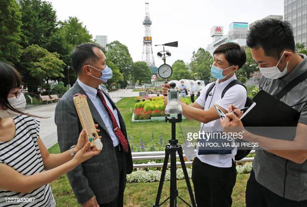 Yasuo Mori , Deputy Executive Director of Tokyo 2020's Games Operations Bureau, and officials check the temperature and wind speed in the field...