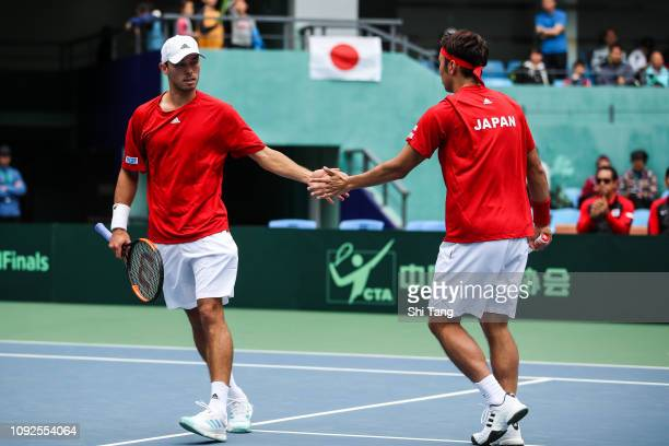 Yasutaka Uchiyama and Ben Mclachlan of Japan react in the Men's Doubles match against Gong Mao Xin and Zhang Ze of China on day two of the 2019 Davis...