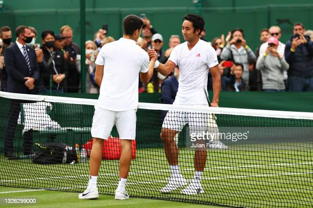 Yasutaka Uchiyama of Japan and Carlos Alcaraz of Spain shake hands at the net after their Men's Singles First Round match during Day Three of The...