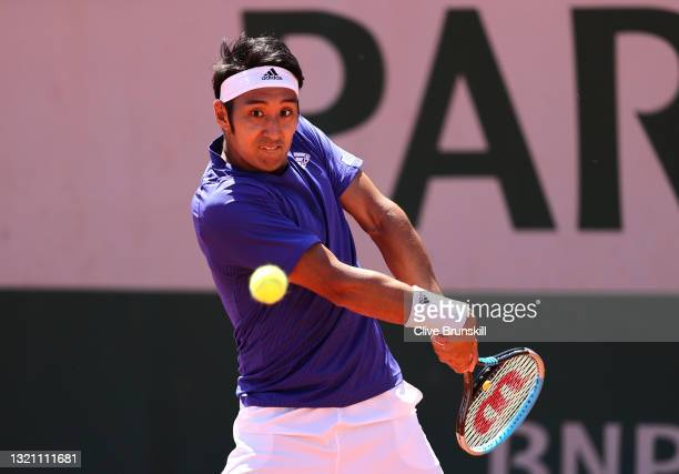 Yasutaka Uchiyama of Japan plays a backhand in their mens first round match against Marco Cecchinato of Italy during day three of the 2021 French...