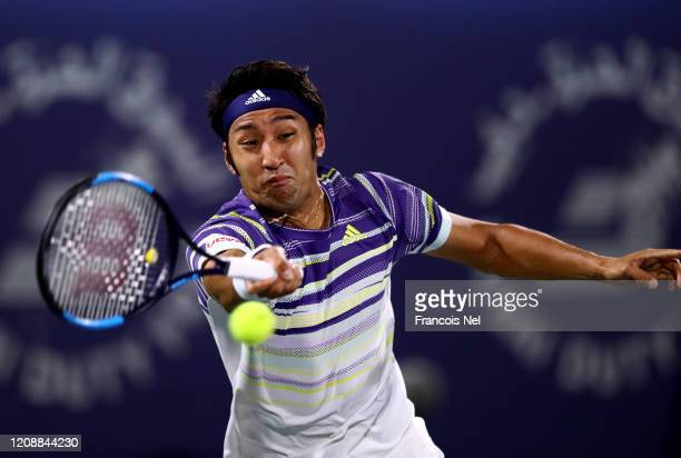 Yasutaka Uchiyama of Japan plays a forehand against Gael Monfils of France during his men's singles match on Day Ten of the Dubai Duty Free Tennis at...