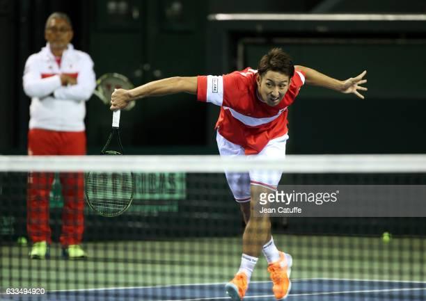 Yasutaka Uchiyama of Japan practices while captain of Team Japan Minoru Ueda looks on ahead of the World Group Davis Cup tie between Japan and France...