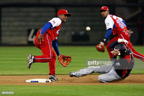 Yasuyuki Kataoka of Japan slides safely into second base after Cuban shortstop Eduardo Paret and Hector Olivera Amaro miss the ball thrown from home...
