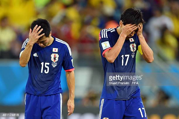 Yasuyuki Konno and Makoto Hasebe of Japan look dejected after the 2014 FIFA World Cup Brazil Group C match between Japan and Colombia at Arena...