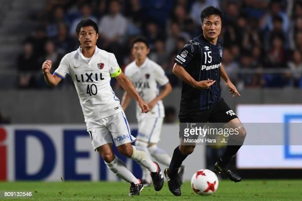Yasuyuki Konno of Gamba Osaka and Mitsuo Ogasawara of Kashima Antlers compete for the ball during the JLeague J1 match between Gamba Osaka and...
