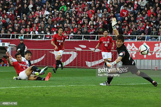 Yasuyuki Konno of Gamba Osaka scores his team's first goal past Shusaku Nishikawa of Urawa Red Diamonds during the JLeague 2015 Championship semi...