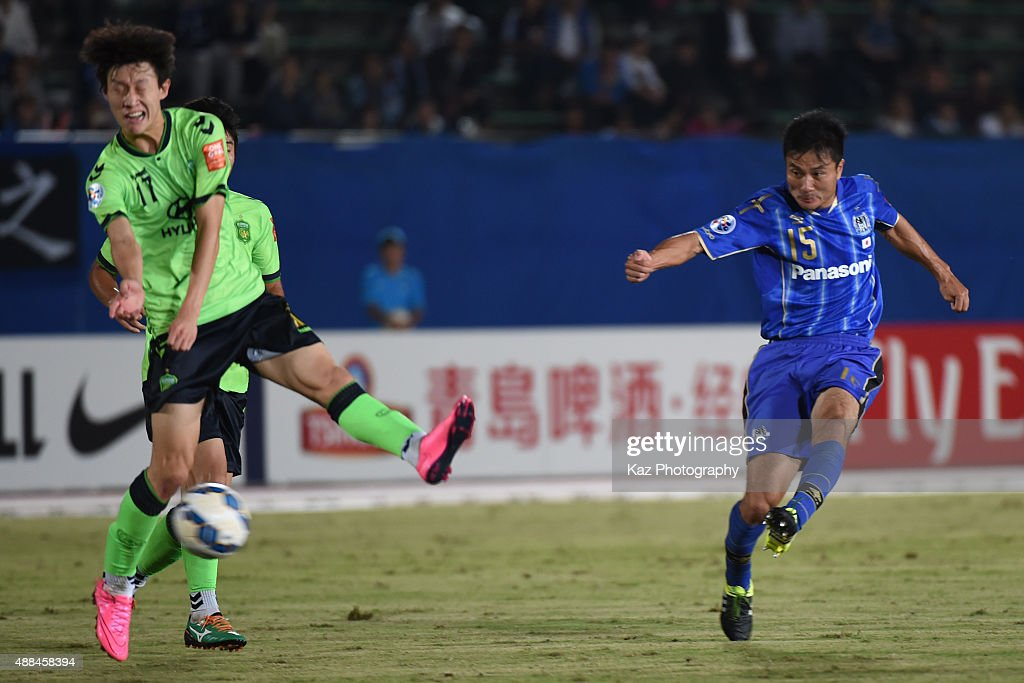 Yasuyuki Konno of Gamba Osaka shoots while Jae Sung Lee of Jeonbuk Hyundai Motors tries to block during the AFC Champions League quarter final match between Gamba Osaka and Jeonbuk Hyundai Motors ]at Expo '70 Stadium on September 16, 2015 in Osaka, Japan.