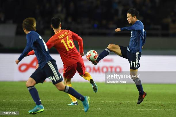 Yasuyuki Konno of Japan and Zheng Zheng of China compete for the ball during the EAFF E1 Men's Football Championship between Japan and China at...