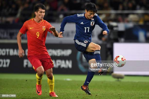 Yasuyuki Konno of Japan controls the ball under pressure of Xiao Zhi of China during the EAFF E1 Men's Football Championship between Japan and China...
