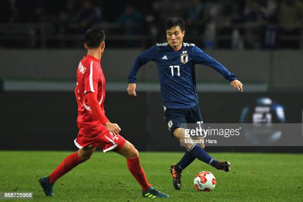 Yasuyuki Konno of Japan takes on Pak Myong Song of North Korea during the EAFF E1 Men's Football Championship between Japan and North Korea at...