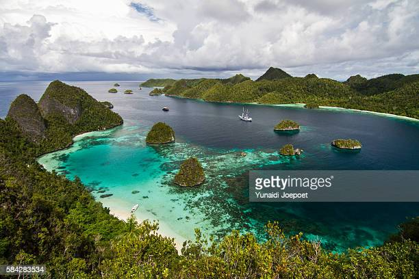 yatch and iconinc view of raja ampat, west papua - raja ampat islands stock photos and pictures