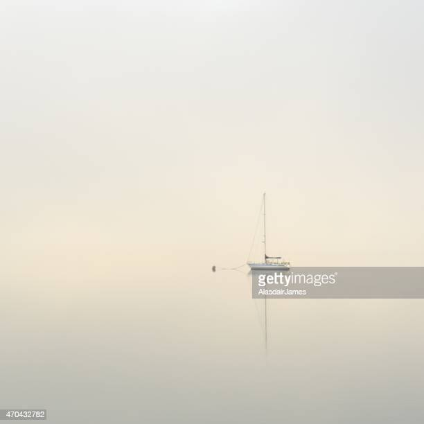 Yatch moored on a calm misty lake at dawn