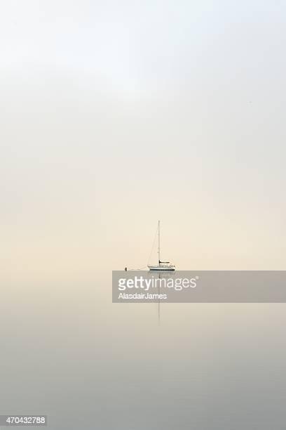 Yatch moored on a calm misty loch at dawn
