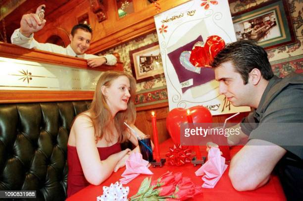 Yate's Wine Lodge's Assistant Manager Mark Jones sprays Pheromone on clients Katy Hudson and Michael AlShewaish 13 February 2000 in Colchester Essex...