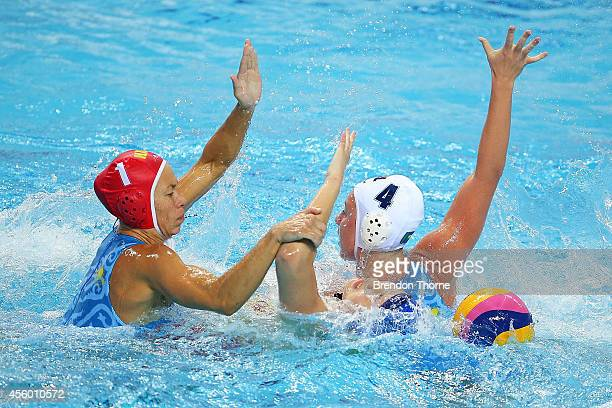 Yating Sun of China competes with Alexandra Zharkova and Anna Turova of Kazakhstan in the Women's Single Round Robin Waterpolo during day five of the...