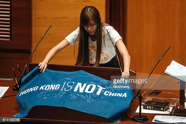 Yau Waiching an incoming lawmaker and member of Youngspiration unfurls a banner that reads 'Hong Kong Is Not China' during an oathtaking ceremony in...