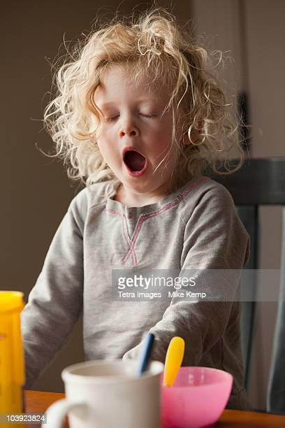 yawning child at the breakfast table - yawning stock pictures, royalty-free photos & images