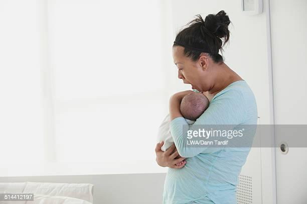Yawning Chinese mother holding newborn