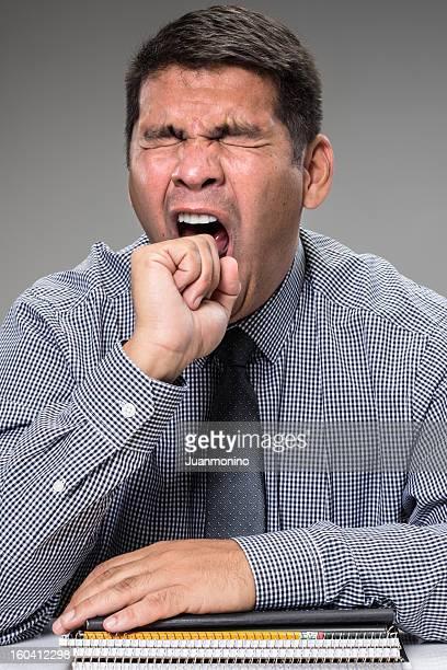 yawning Hispanic man wearing a tie