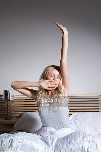 Yawning woman stretching in bed