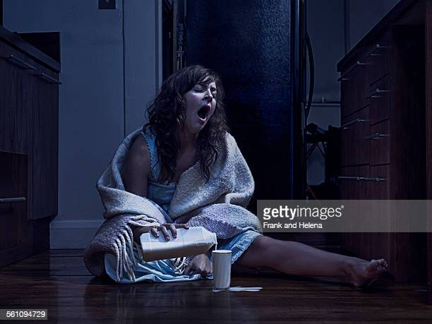 Yawning woman wrapped in blanket sitting on kitchen floor pouring milk at night