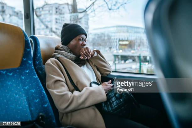 Yawning young woman traveling by bus