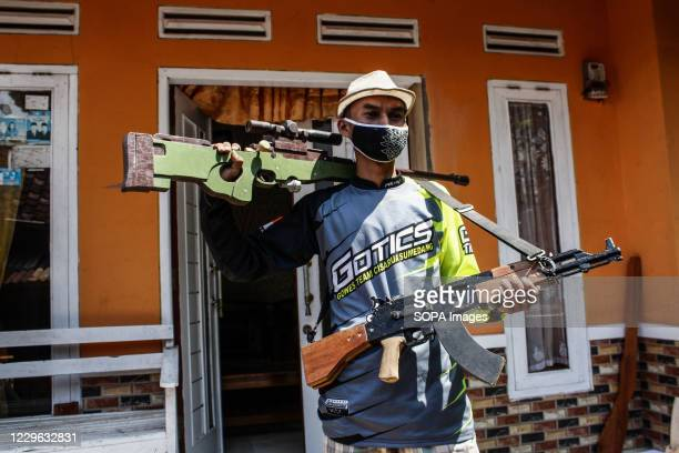 Yaya Saepuloh, wearing a face mask poses for photo while holding wooden replicas of real guns inspired by online game in Cipameungpeuk Village....