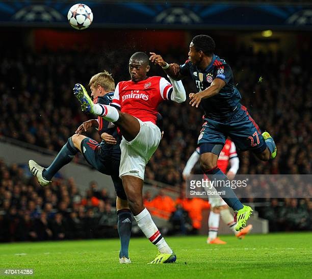Yaya Sanogo of Arsenal is marshalled by Toni Kroos and David Alaba of Bayern Muenchen during the UEFA Champions League Round of 16 first leg match...