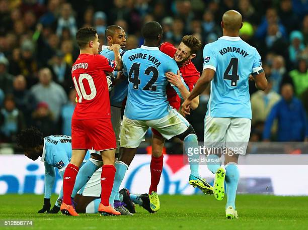 Yaya Toure of Manchester City and Adam Lallana of Liverpool clash as players intervene during the Capital One Cup Final match between Liverpool and...