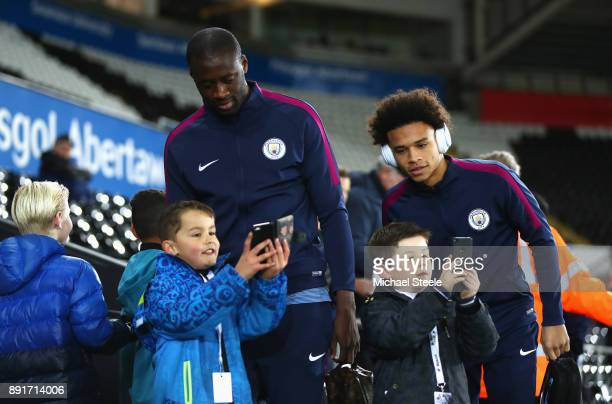 Yaya Toure of Manchester City and Leroy Sane of Manchester City take photos with fans as they arrive prior to the Premier League match between...