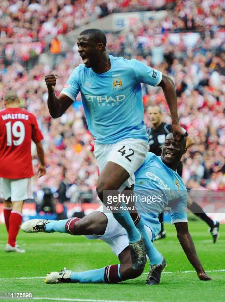 Yaya Toure of Manchester City celebrates as team mate Mario Balotelli tries to trip him up after he scored during the FA Cup sponsored by EON Final...
