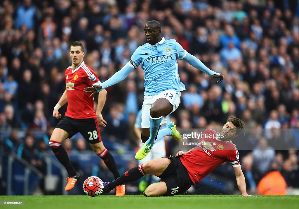 Yaya Toure of Manchester City evades Michael Carrick of Manchester United during the Barclays Premier League match between Manchester City and Manchester United at Etihad Stadium on March 20, 2016 in Manchester, United Kingdom.