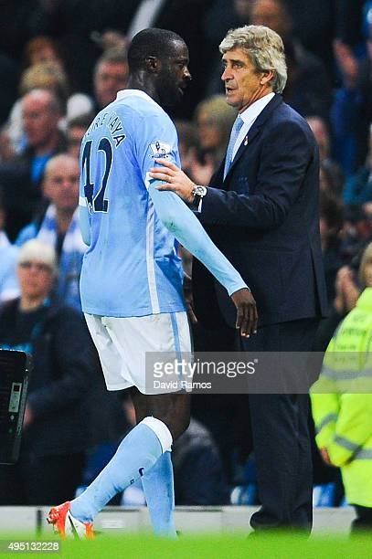 Yaya Toure of Manchester City FC talks with his Head Coach Manuel Pellegrini of as he is being substituted during the Barclays Premier League match...