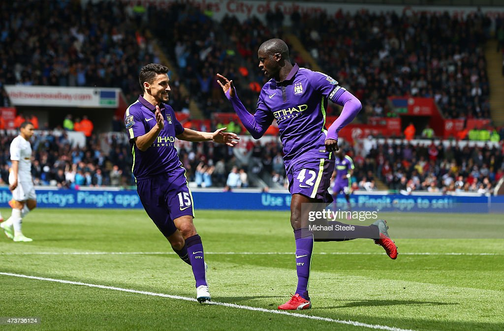 Yaya Toure of Manchester City is congratulated by teammate Jesus Navas of Manchester City after scoring his team's third goal during the Barclays Premier League match between Swansea and Manchester City at the Liberty Stadium on May 17, 2015 in Swansea, Wales.