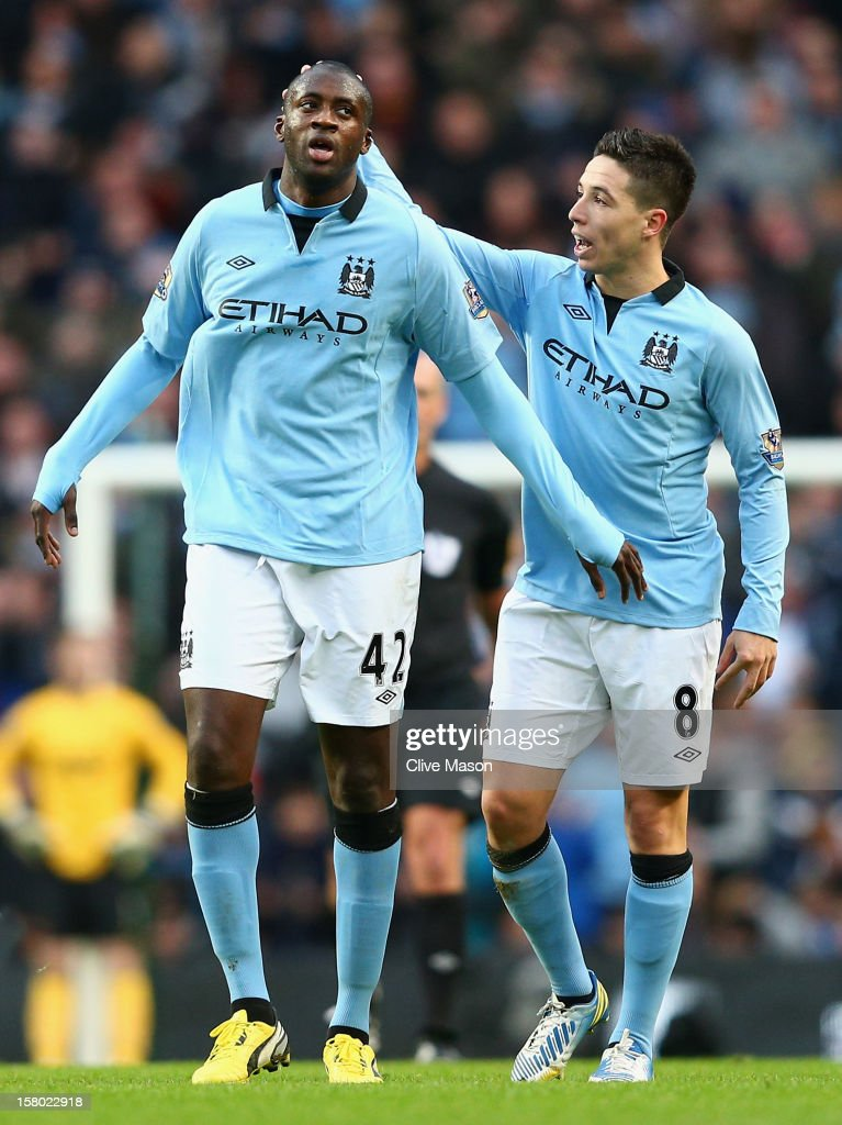 Yaya Toure of Manchester City is congratulated by team-mate Samir Nasri (R) after scoring his team's first goal to make the score 1-2 during the Barclays Premier League match between Manchester City and Manchester United at the Etihad Stadium on December 9, 2012 in Manchester, England.