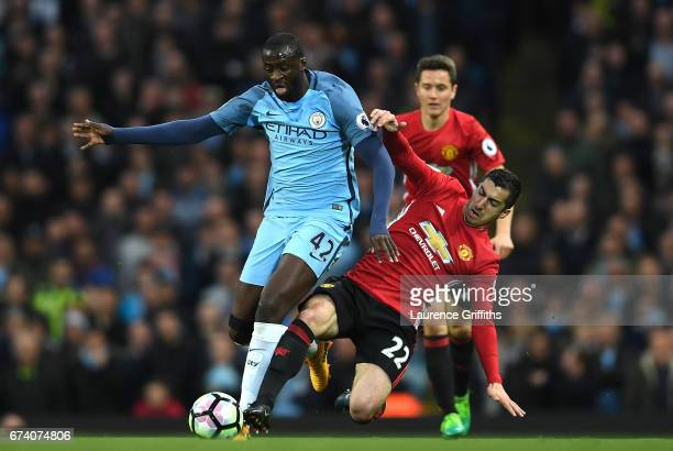 Yaya Toure of Manchester City is tackled by Henrikh Mkhitaryan of Manchester United during the Premier League match between Manchester City and...
