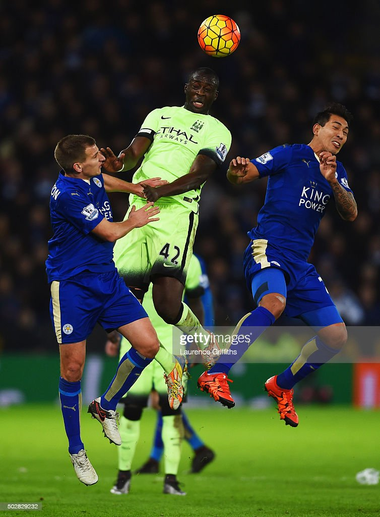 Yaya Toure of Manchester City jumps between Marc Albrighton (L) and Leonardo Ulloa of Leicester City (R) during the Barclays Premier League match between Leicester City and Manchester City at The King Power Stadium on December 29, 2015 in Leicester, England.