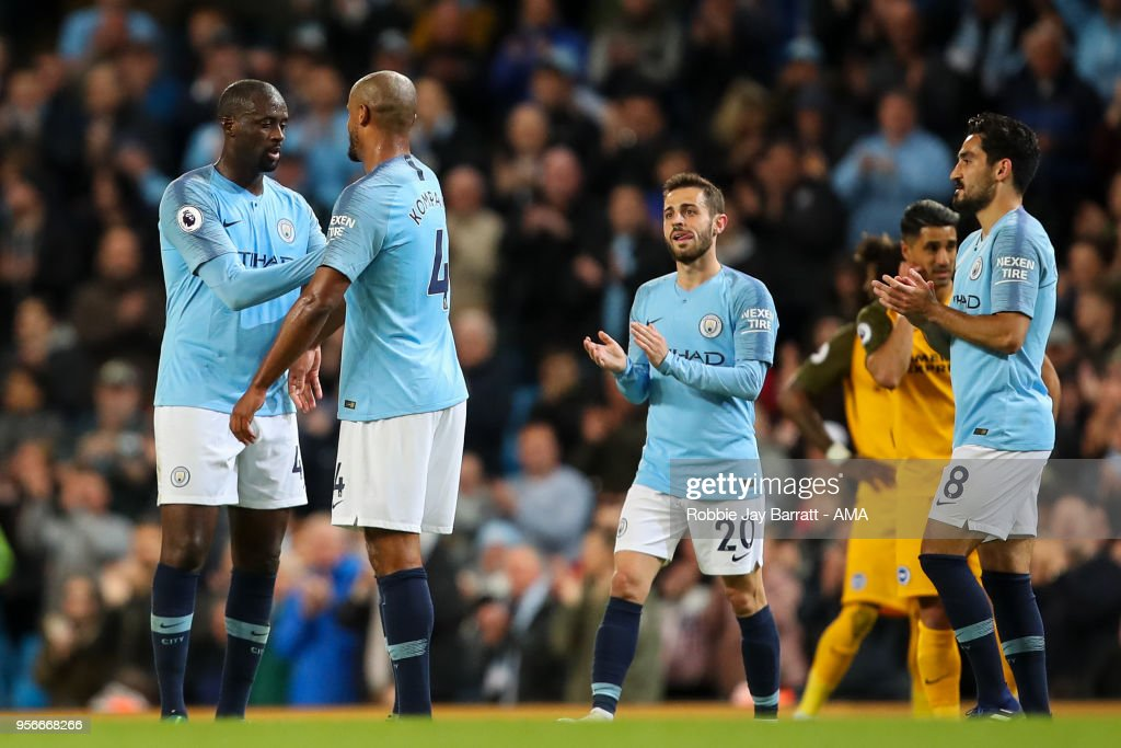 Yaya Toure of Manchester City passes Vincent Kompany of Manchester City the captain arm band as he is substituted off for his final appearance for the club during the Premier League match between Manchester City and Brighton and Hove Albion at Etihad Stadium on May 9, 2018 in Manchester, England.