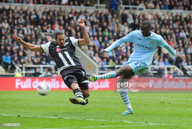 Yaya Toure of Manchester City scores to make it 20 under pressure from Jonas Gutierrez of Newcastle United during the Barclays Premier League match...