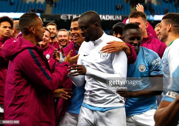 Yaya Toure of Manchester City shakes hands with Danilo of Manchester City as he mobbed by his team mates during the Premier League match between...